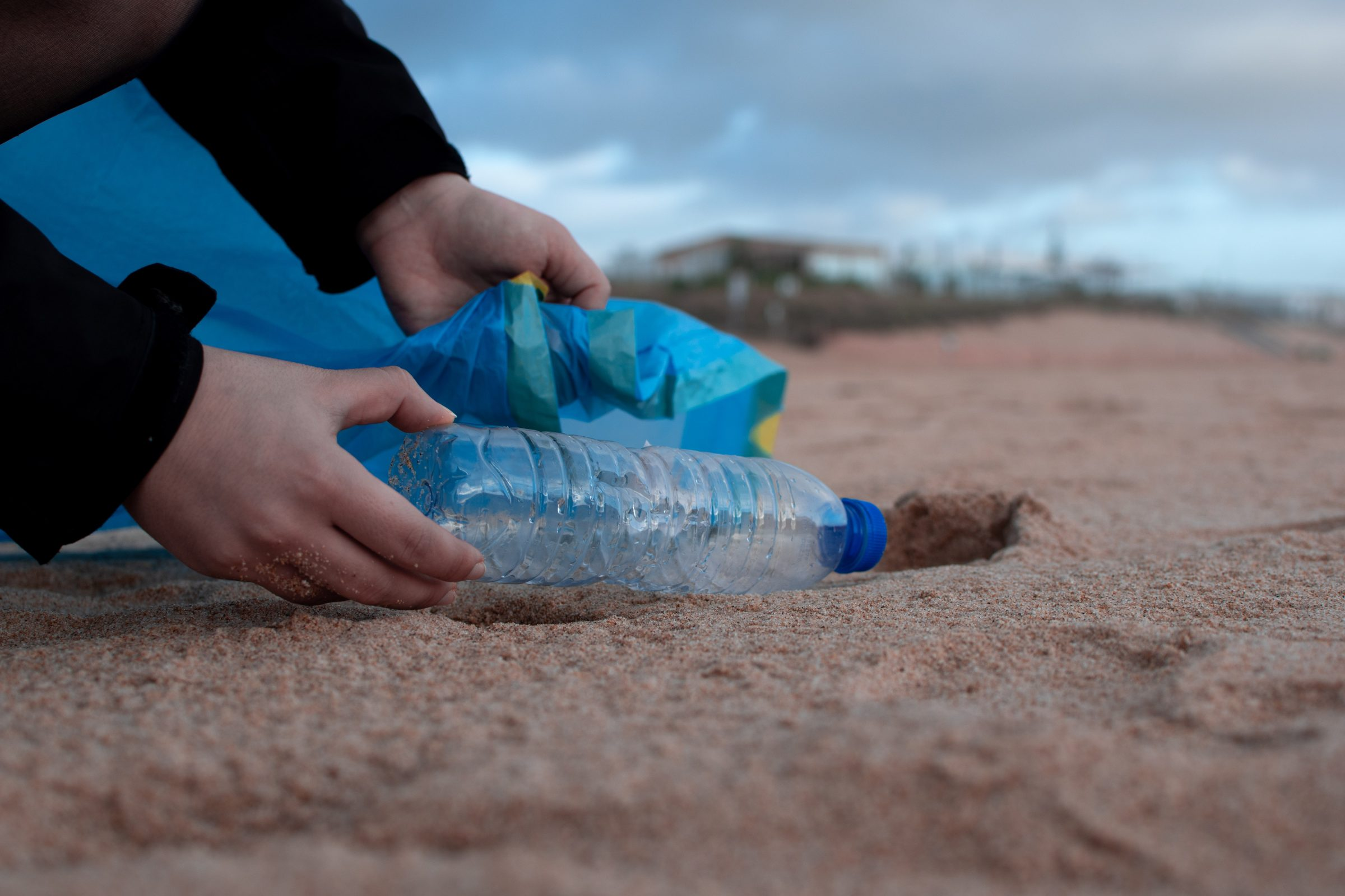 Picking up a bottle of rubbish on a beach