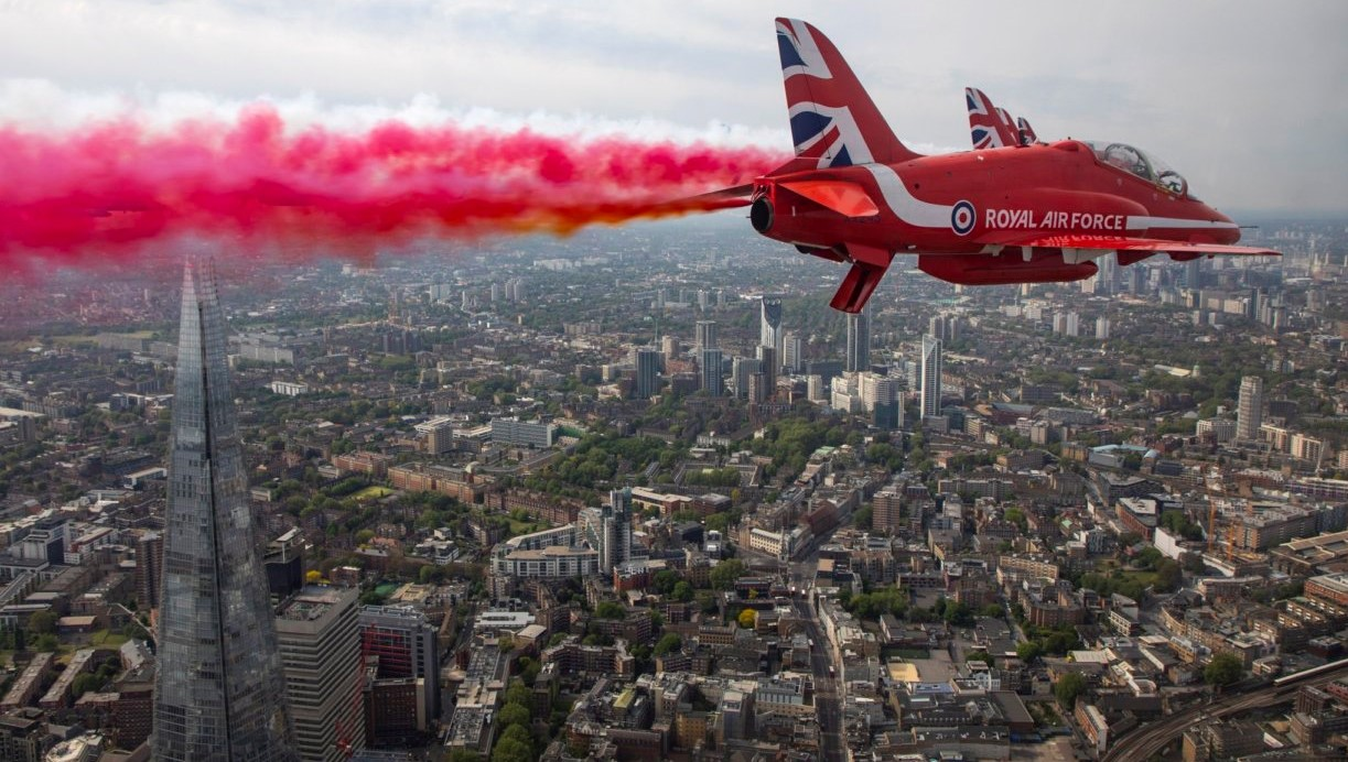 Red Arrow flying above a city